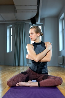 Молодая спортивная женщина практикующих йогу, разработка, ношение спортивной одежды, брюки и топ, закрытый крупным планом, студия йоги