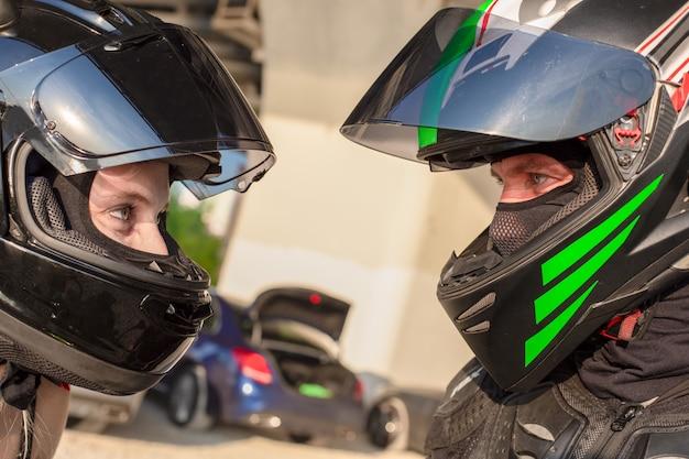 ヘルメットのバイカーの男女の肖像画はお互いを見てください。オートバイの愛の概念。エクストリームライダー
