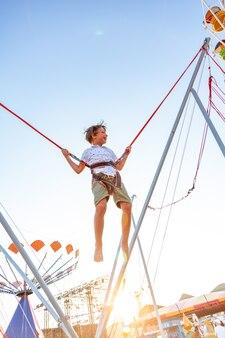 Улыбающийся возбужденный мальчик прыгает на батуте со страховкой.