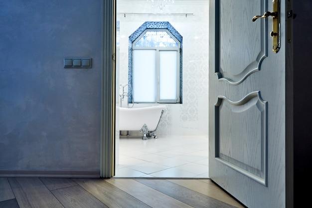 美しいインテリアのモダンなバスルーム。インテリアアーキテクチャ。開いたドアを通して見る