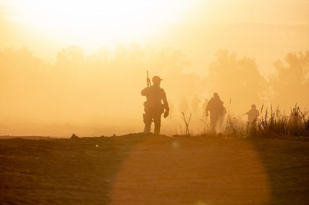 Силуэт действия солдат ходьбе держать оружие дым и закат и баланс белого корабля эффект темного стиля арт