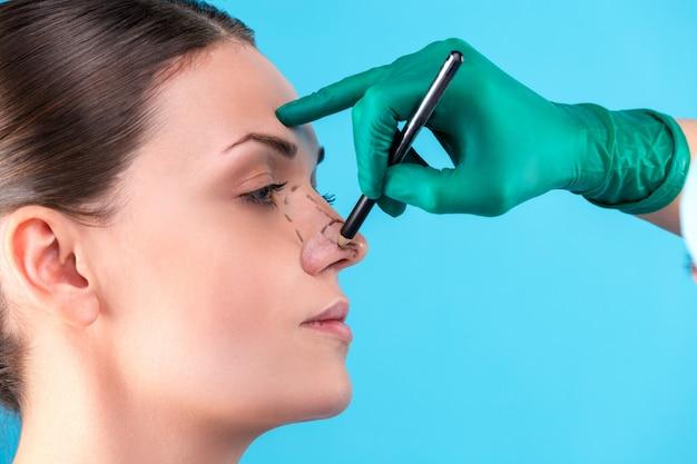 美容整形外科医がオフィスで女性のクライアントを調べます。医師はマーカー、整形手術の前にまぶた、眼瞼形成術で線を引きます。外科医や美容師の手が女性の顔に触れます。鼻形成術