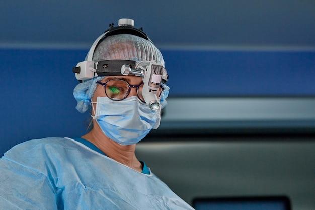 操作中に防護マスクと帽子を身に着けている女性外科医の肖像画を閉じます。ヘルスケア、医学教育、手術のコンセプト。