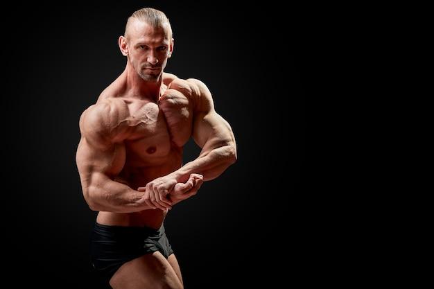 アスレチック男がポーズします。黒い壁に完璧な体格を持つ男の写真。強さと動機