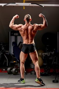 アスレチック男がポーズします。黒い壁に完璧な体格を持つ男の写真。背面図。強さと動機