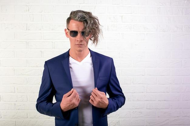 Портрет стильный бизнесмен с вьющимися длинными волосами в солнцезащитные очки, улыбаясь в камеру на белой стене