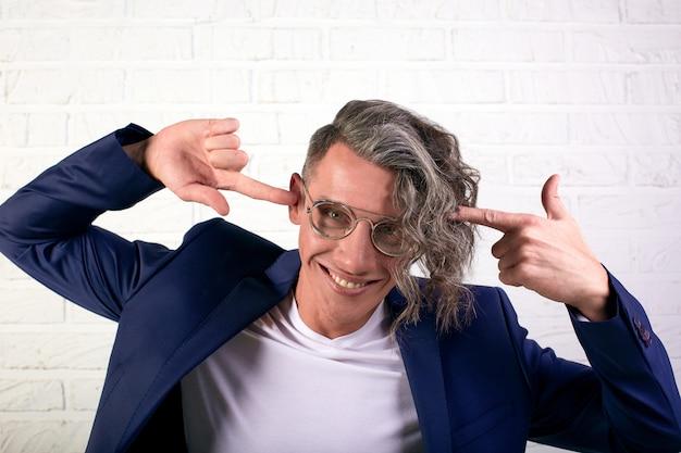 Портрет стильный бизнесмен с вьющимися длинными волосами в солнцезащитные очки, улыбаясь в камеру на белой стене. держит его за голову. вынос мозга