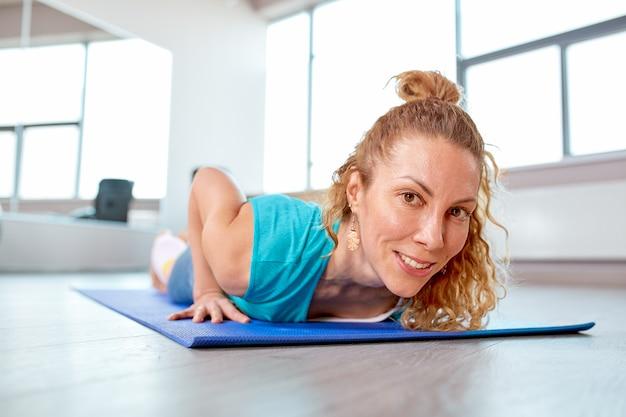 ジムで苦労して運動の魅力的な女性。トレーニングのコンセプト、スポーツ、トレーニングプロセス