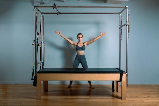 Девушка тренера нёба представляя для реформатора в спортзале. фитнес-концепция, специальное фитнес-оборудование, здоровый образ жизни, пластик. копирование пространства, спортивный баннер для рекламы.