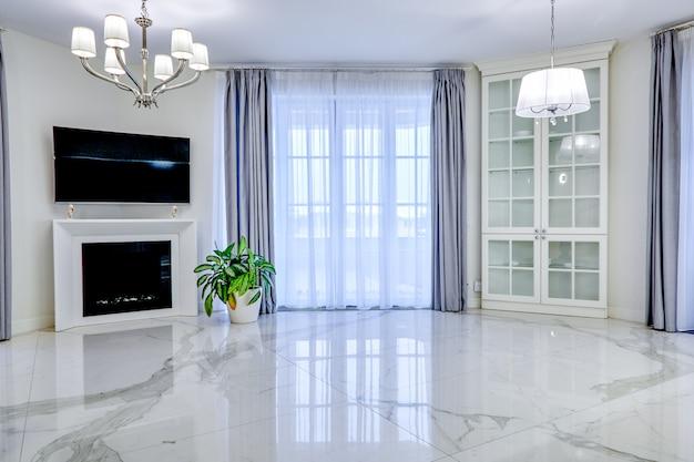 Минималистичный интерьер гостиной комнаты в светлых тонах с мраморным полом, большими окнами и камином под телевизором.