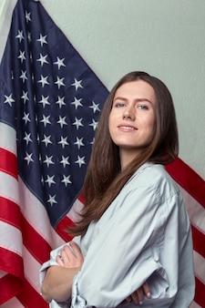Портрет красивой девушки с патриотическим взглядом в рубашке на американском флаге крупным планом