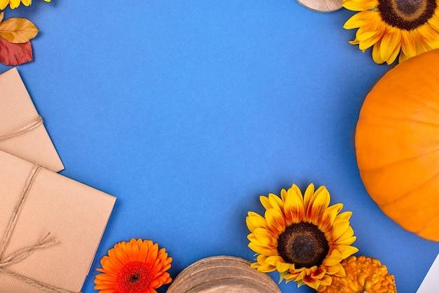 Вид сверху ручной подарочной коробке, желтые и оранжевые цветы и тыквы на синем фоне.