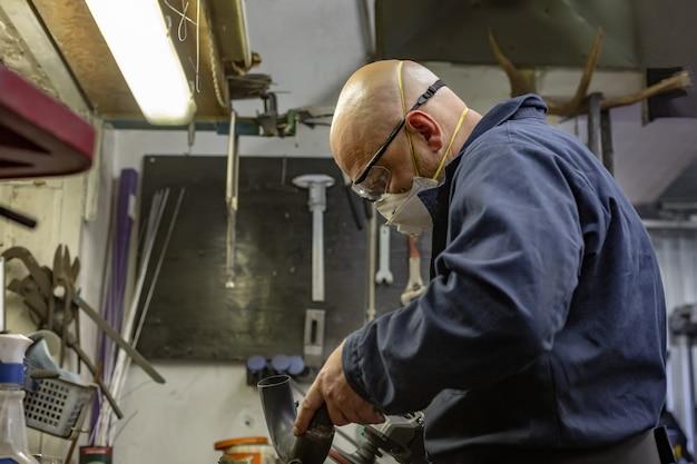 ガレージでバイクを修理してそれをカスタマイズするのに働いている人の側面の肖像