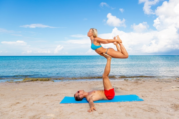 若いカップルの女性と一緒にフィットネスヨガ運動をしているビーチでの男性。強さとバランスのアクロヨガ要素