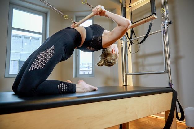 Тренажерный зал женщина пилатес растяжения спорта в реформатор кровать инструктор девушка. здоровая улыбающаяся женщина, носящая купальник, практикующий пилатес