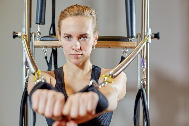 Тренажерный зал женщина пилатес растяжения спорта в реформатор кровать инструктор девушка. выборочный фокус на руках