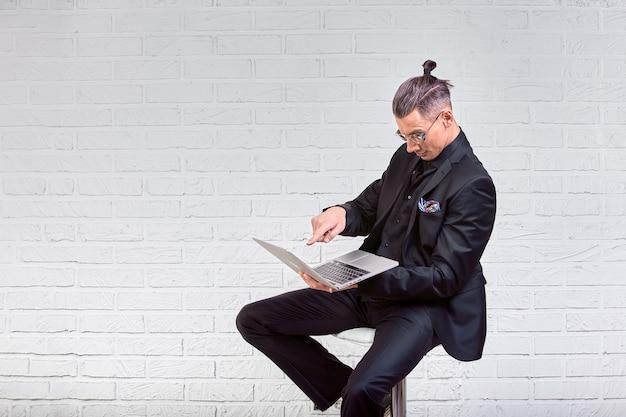 メガネとスーツのラップトップを手で押し、何かを書くのハンサムな実業家。側面図。