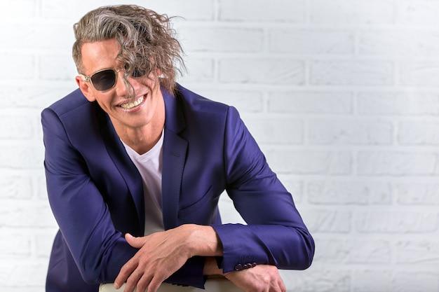 Стильный бизнесмен с вьющимися длинными волосами в темных очках, сидя на стуле на белой стене