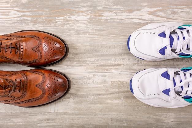 木製の床にメンズの古典的な茶色の革の靴とスニーカー。メンズブラウンシューズ。