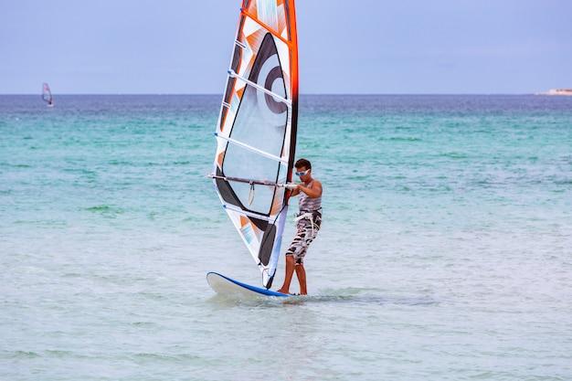 美しい晴れた日に波に乗るサーファー。風と海のサーフィンを楽しんでいる若い男。