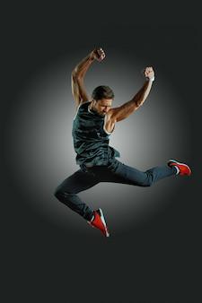 うれしそうなアスレチックビルド男が黒い壁に空気中をジャンプします。ライフスタイルとスポーツのコンセプト