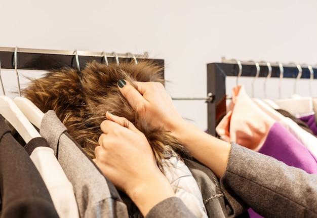 ファッションモールで買い物をする女性、新しい服を選ぶ