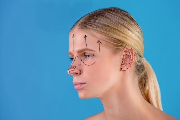 美容師は女性の顔に修正線を描画します。形成外科手術の前。青に分離
