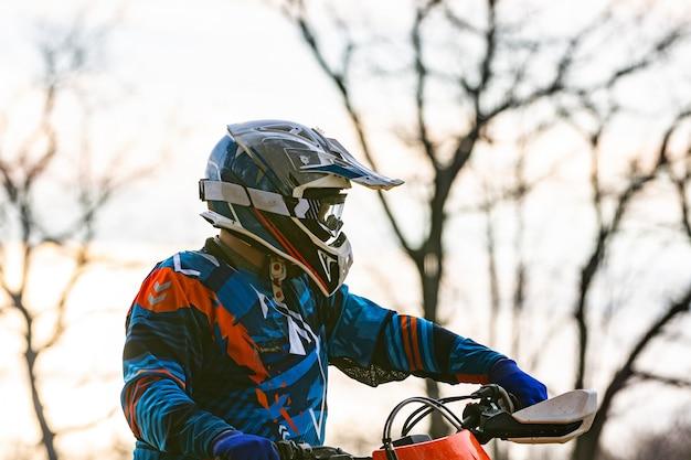 Мужчина верхом на мотокроссе в защитном костюме