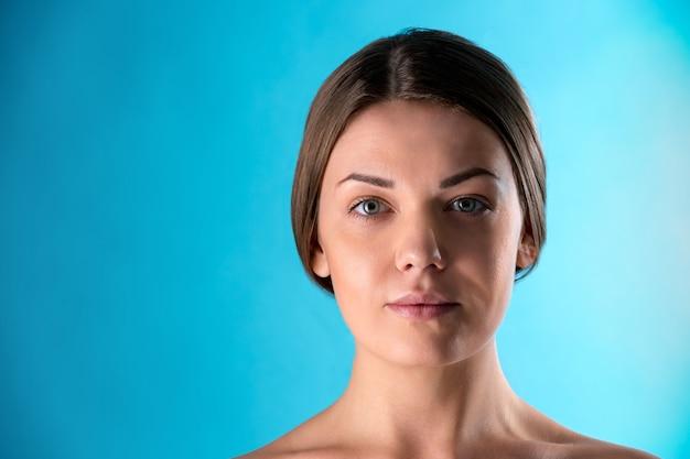 美しい女性の顔。青い壁に笑みを浮かべてブルネットの若い女性の美しさの肖像画。パーフェクトフレッシュスキン。若さと肌ケアのコンセプトです。