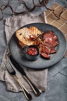 チャバタのトマトソースが入ったジューシーなローストビーフを美しくスライスし、皿に並べます。
