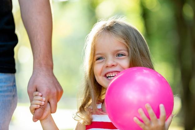 Счастливый отец и маленькая девочка гуляют, держа в руке в парке летом