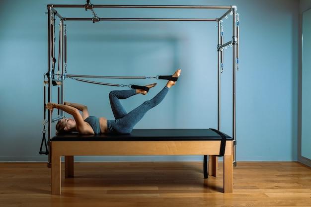 若い女の子はベッドのリフォーマーでピラティスのエクササイズをします