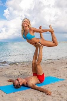 若いカップルの女性と一緒にフィットネスヨガ運動をしているビーチでの男性。