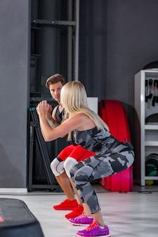 Глубокий присед. фитнес пара в спортивной одежде, делать приседания в тренажерном зале.