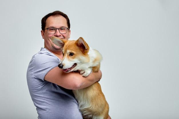 Собака лежит на плече своего владельца. валлийский корги в руках своего владельца на белой стене. понятие о людях и животных.