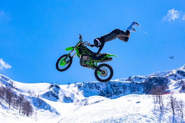 飛行中のオートバイのレーサー、ジャンプして、雪に覆われた山々に対して跳躍板に飛び立つ