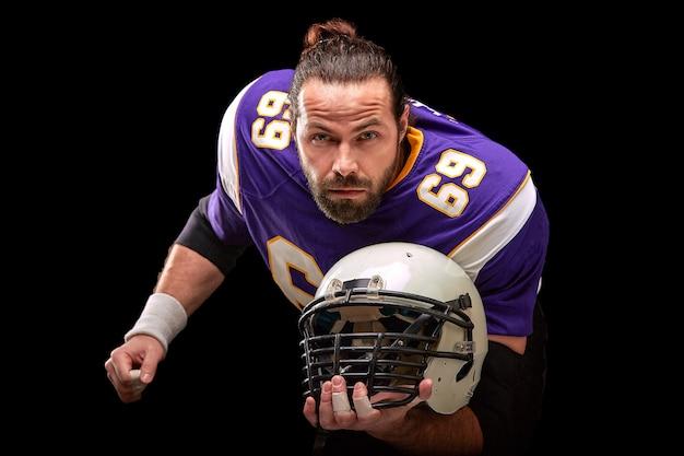 手にヘルメットを持つアメリカンフットボール選手の肖像画をクローズアップ