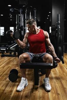 ジムで若いスポーツ選手のフィットネスモデルは、ダンベルで上腕二頭筋を振る。スポーツの動機、低いキー、高いコントラスト。健康的なライフスタイル、生活の動き、コピースペースの概念。