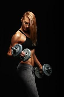 ヤングは、彼女の手にダンベルを持つスポーツ用品の女性、スポーツエンボス女性の身体、黒い空間、ハードライトに合います。コピースペース、スポーツバナー