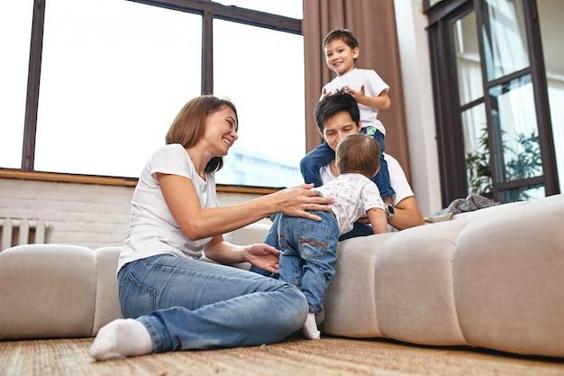 Международная семья дома на диване, обнимаюсь и наслаждаюсь жизнью. счастливая семейная жизнь