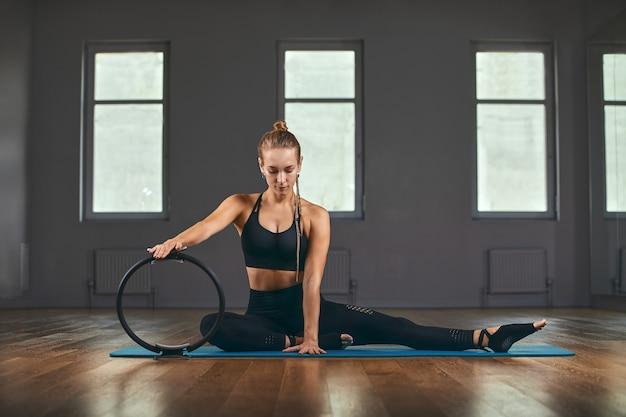 Фитнес-тренер показывает упражнения с резиновым расширителем. мотивация для красивого тела. фитнес баннер, копия пространства.