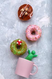 コーヒーのマグカップと灰色のスペースに色付きのドーナツ。平面図、コーヒーからの煙を模したマグカップにドーナツが広がっています。コンセプトデザート、甘いドーナツ。