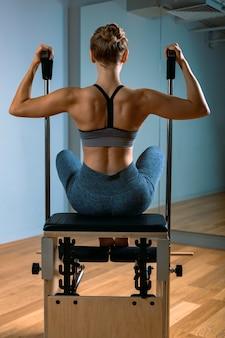 Пилатес женщина в реформатор, делать упражнения на растяжку в тренажерном зале. фитнес-концепция, специальное фитнес-оборудование, здоровый образ жизни, пластик. копировать пространство, спортивный баннер для рекламы