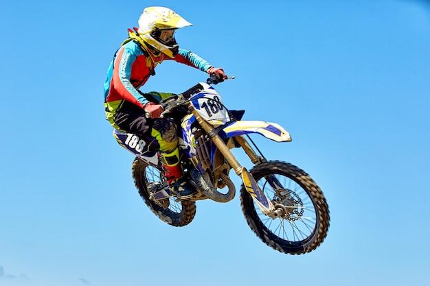 Экстрим, мотоциклетные прыжки. мотоциклист совершает экстремальный прыжок на фоне неба.