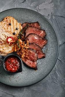 ジューシーなローストビーフとチャバタのトマトソースが美しくスライスされ、皿に並べられます