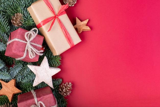 クリスマスの組成物。赤いクリスマスの装飾、おもちゃのギフトボックスとモミの木の枝