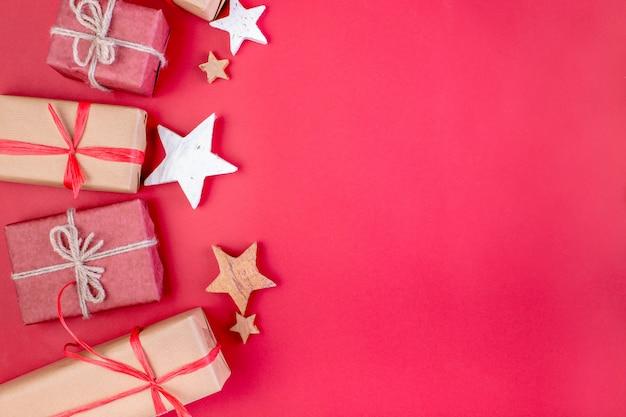 クリスマスの組成物。赤いクリスマスの装飾、星、赤い背景の上のギフトボックス