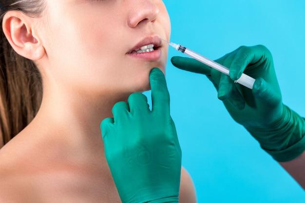 Красивая женщина лицо и косметолог руки со шприцем