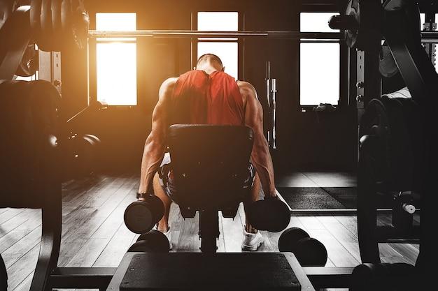 スポーツの動機。ジムシアター。ジムでダンベルで演習を行う筋肉男ボディービルダー。運動体、健康的なライフスタイル、フィットネスの動機、肯定的なボディ。