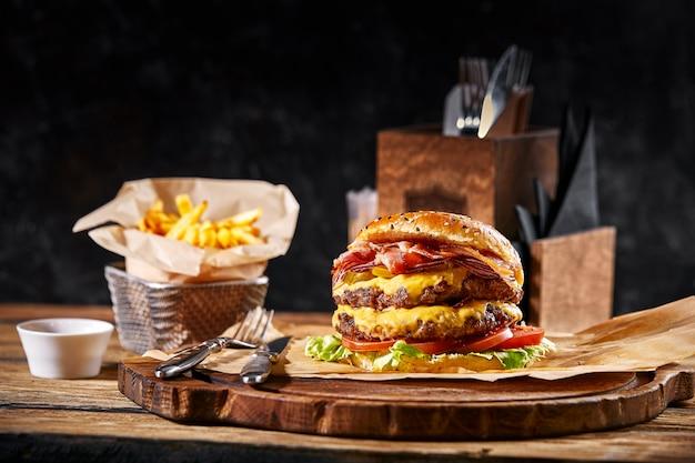 木製のテーブルにビールと紙枕に新鮮でジューシーなハンバーガー。暗い背景、伝統的なアメリカ料理。ジャンクフード、...